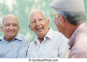 Active retirement, group of three old male friends talking and laughing on bench in public park