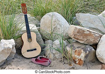 guitar on rocks in sand