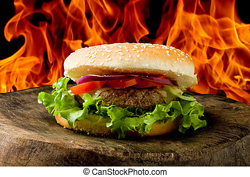 photo of delicious american hamburg on wooden table in front of a flame background