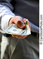 Hand of a businessman offering money