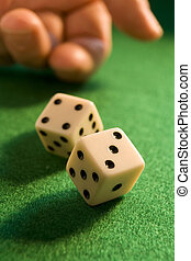 hand rolling dice onto a green baize