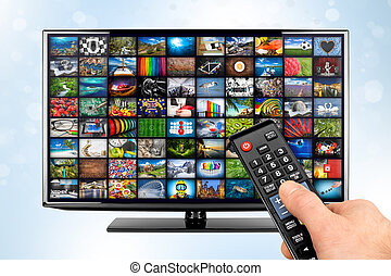 hand with remote on black flat tv screen display with picture movie gallery backdrop. television front of white blue bokeh background. Computer multimedia streaming internet and cloud concept