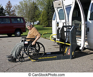 handicapped man in a wheelchair backing into a vehicle lift