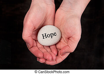 Hands holding a rock with engraved word Hope