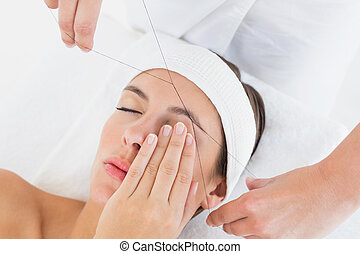 Close up of a hands threading beautiful woman's eyebrow