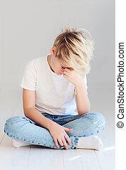 handsome teenager boy sitting on the floor