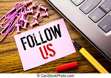 Handwritten text showing Follow Us. Business concept for Social Media Marketing written on pink sticky note paper on the wooden background next to keyboard. With red pen.