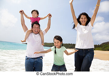 happy asian family jumping on the beach