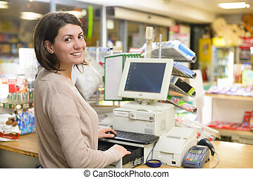 Young woman at cash register in a store