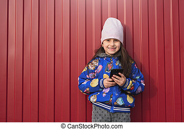 Happy girl kid with smartphone in hands on a red background in the street. Dressed in a blue jacket and smiling.