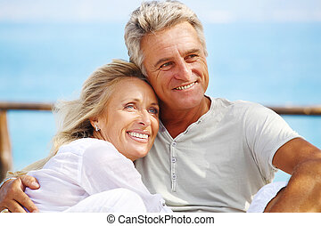 Happy mature couple smiling and embracing outdoors.