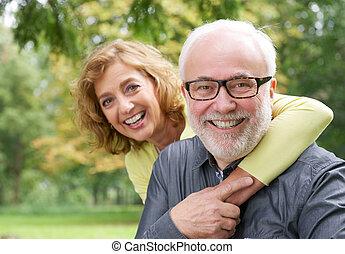 Closeup portrait of a happy older woman embracing smiling older man