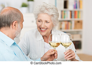 Happy senior couple celebrating clinking their glasses of white wine and smiling at each other as they sit together on a sofa indoors