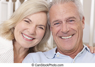 Happy senior man and woman couple sitting together at home smiling and happy