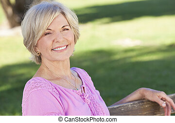 An attractive elegant and happy senior woman sitting outside and smiling