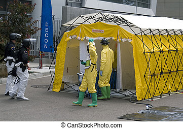 Hazmat crew members and a SWAT policemen awaiting a victim in a decontamination shower.