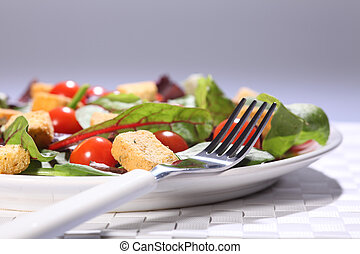Healthy green salad in a white plate, set on a weaved place mat. Salad includes cherry tomatoes and croutons. Fork placed on the plate.