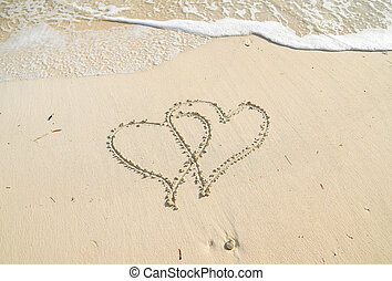 hearts in sand with surf