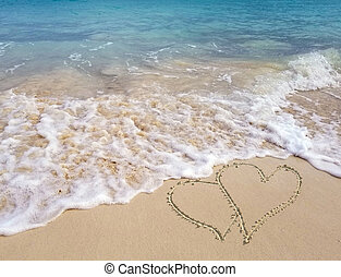 hearts in seashore sand with ocean surf