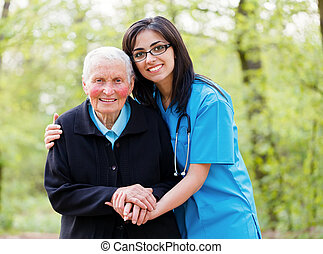 Portrait of caring nurse helping elderly lady holding her hands.