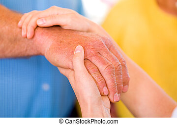Close up photo of elderly woman hand hold by young carer hands