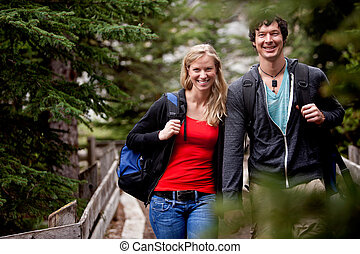 A man and woman on a hike in the forest, smiling at the camera