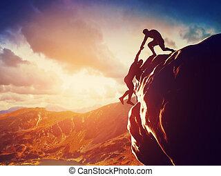 Hikers climbing on rock, mountain