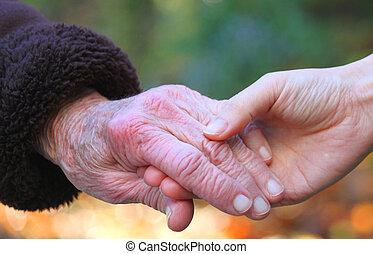 Holding seniors hand in autumn