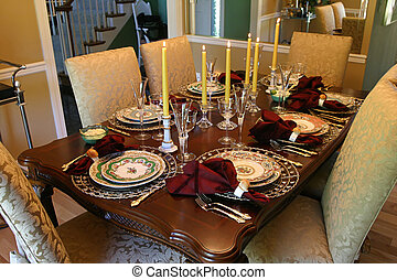 a table set with fine china and candles for the holiday meal
