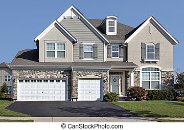 Home in suburbs with three car stone garage