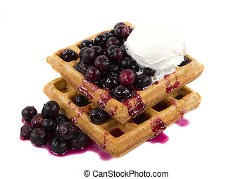 Homemade whole wheat waffles with fresh blueberries, honey and cream