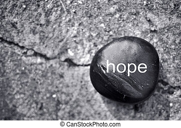 The word hope on a zen stone against concrete