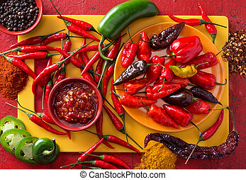 A group of bright colorful hot peppers on a red background.