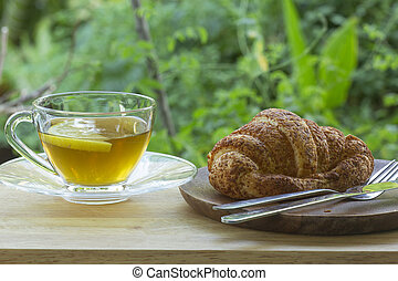 Hot Tea with croissant bread on  Wooden Bar