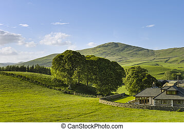 A large house set in green, rural countryside with hills in the background.