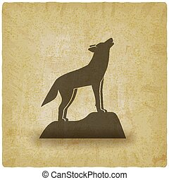 Howling wolf stands on rock vintage background
