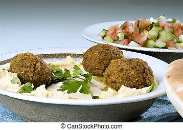 Falafel balls with hummus, arabic salad, pita and a tahini sauce.