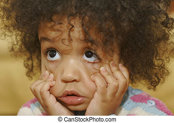 A beautiful mixed race little girl pulling a face.