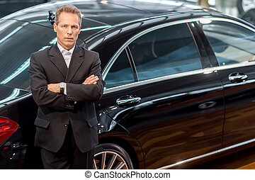 I love luxury cars. Top view of confident grey hair man in formalwear leaning at the car and looking at camera