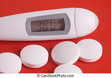 Thermometer with some pills on red background - Thermometer mit Tabletten auf rotem Hintergrund