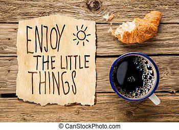 Inspirational early morning breakfast of a half eaten fresh croissant with filter coffee and a handwritten note - Enjoy the little things - reminding us to appreciate even the simple moments in life