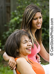 Hispanic teenage girl with African American mother sitting together