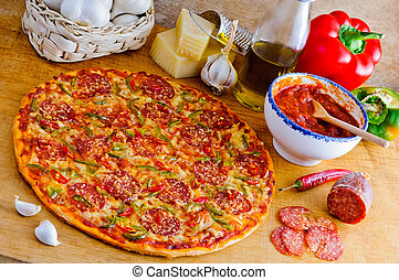 Traditional italian pepperoni pizza and ingredients on a wooden table