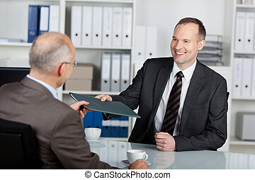 Portrait of a manager interviewing a male applicant in his office