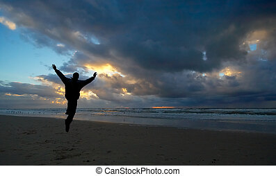 A person jumping for joy during sunset
