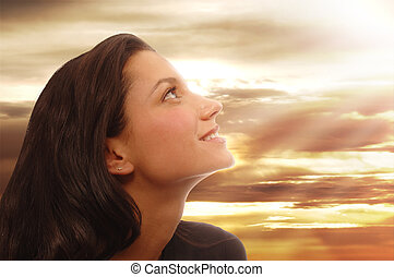 Beautiful young woman looking to heaven with a peaceful expression