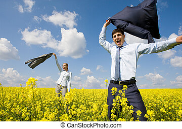 Portrait of happy business partners happily screaming in yellow meadow