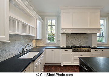 Kitchen in new construction home with black countertops