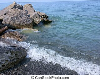 An peaceful place on the lake with rocks and small waves.