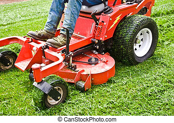 Man on a riding lawn mower that has grass stuck to the wheels. Spring and summer outdoor maintenance.